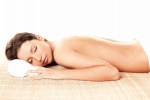 Portrait of Fresh and Beautiful brunette woman laying on bamboo mat